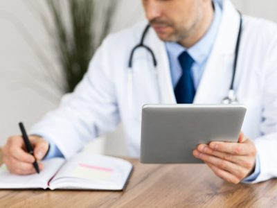 Healthcare, Medical Care And Technology Concept. Male doctor working in office at clinic, writing with pen in notebook, holding and using digital tablet, checking appointment schedule