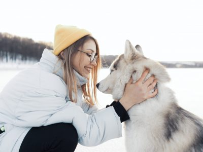 Happy young girl playing with siberian husky dog in winter park. They walk on a frozen lake